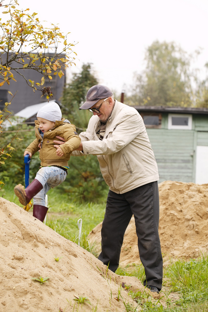 Grandpa helps grandson to get on a sand hill