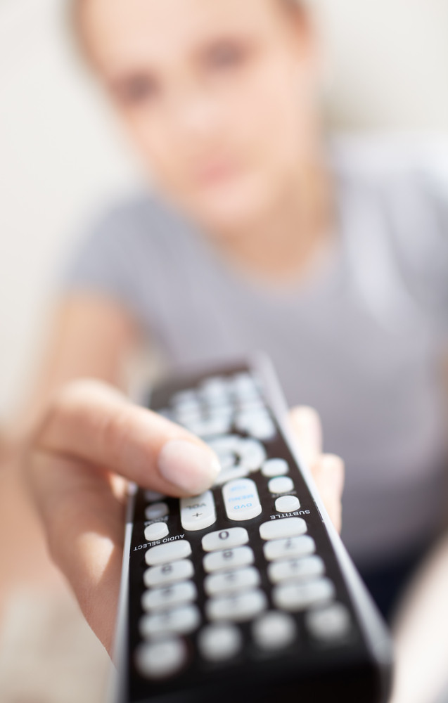 Young woman with remote watching tv