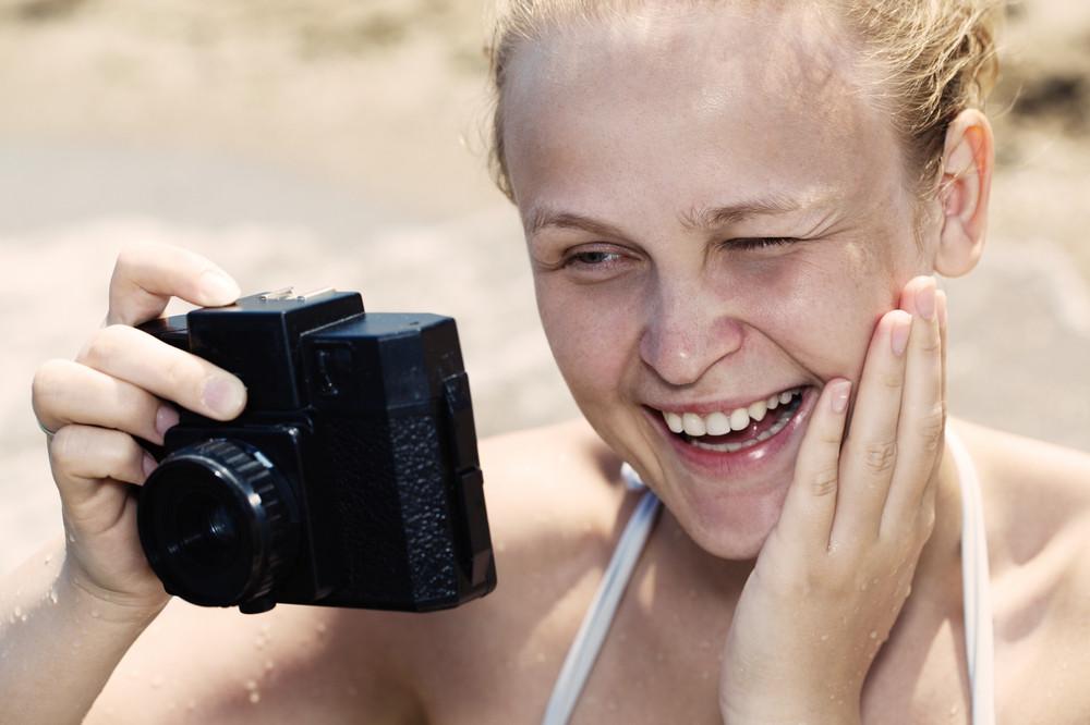 Woman laughing as she views a photo