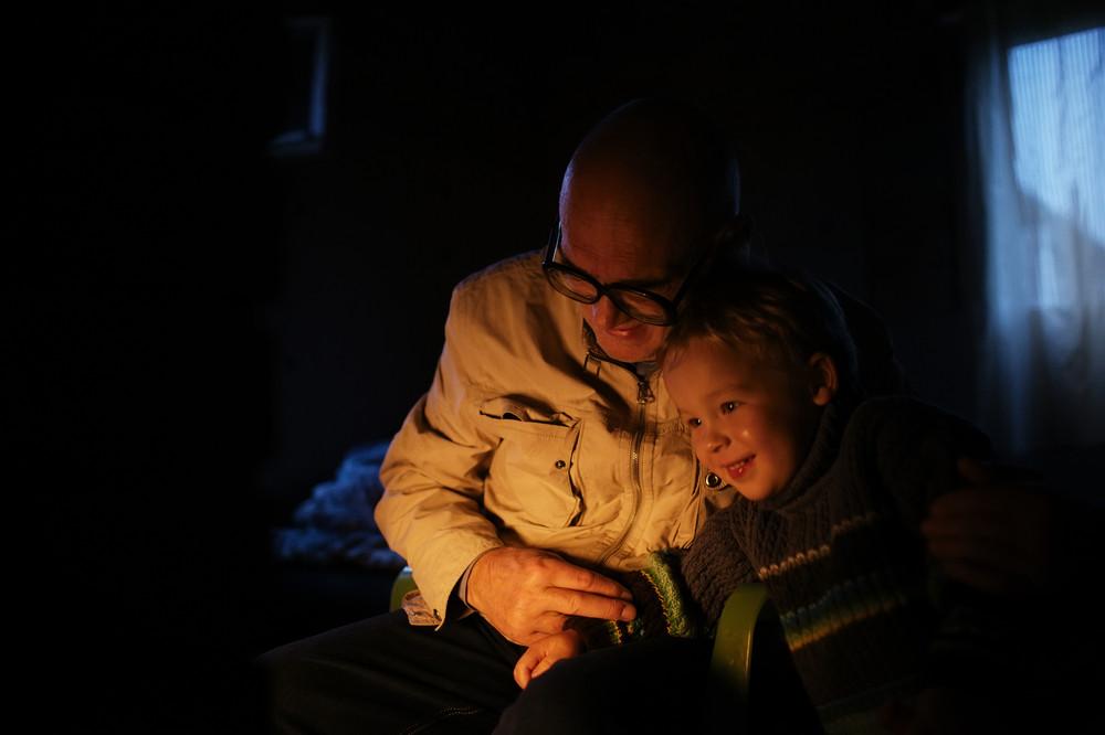 Grandfather hugs his grandson near fireplace