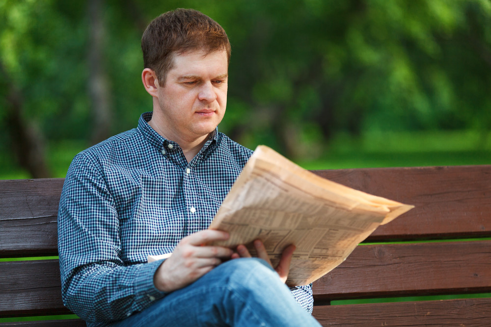 Man reads newspaper on bench in the park