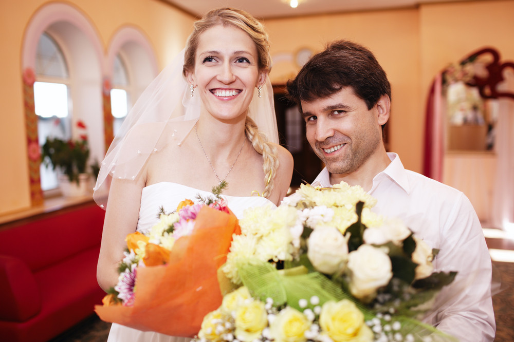 Smiling bride and groom with bouquets of flowers
