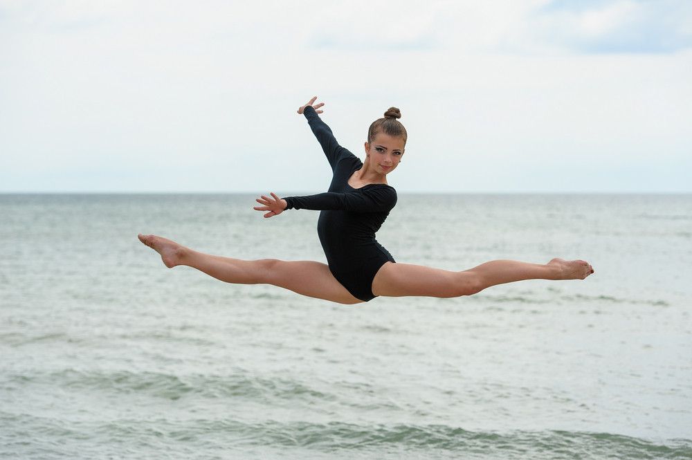 Gymnast dancer jumping on the sea beach