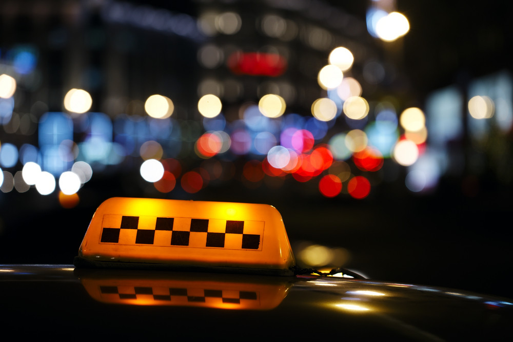 Illuminated taxi cab sign on a city street