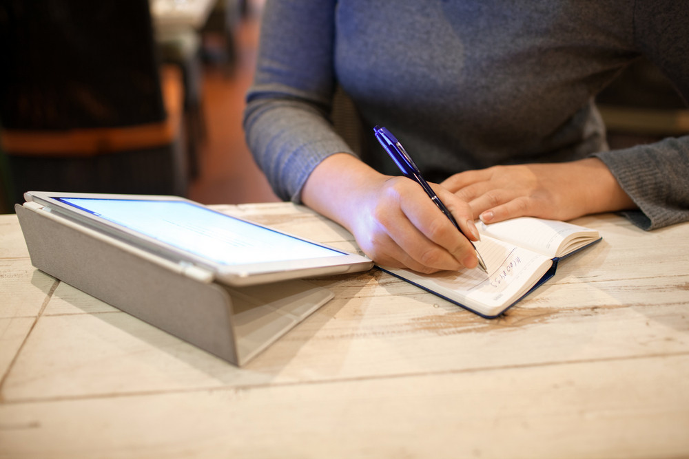 Woman taking down information in notebook
