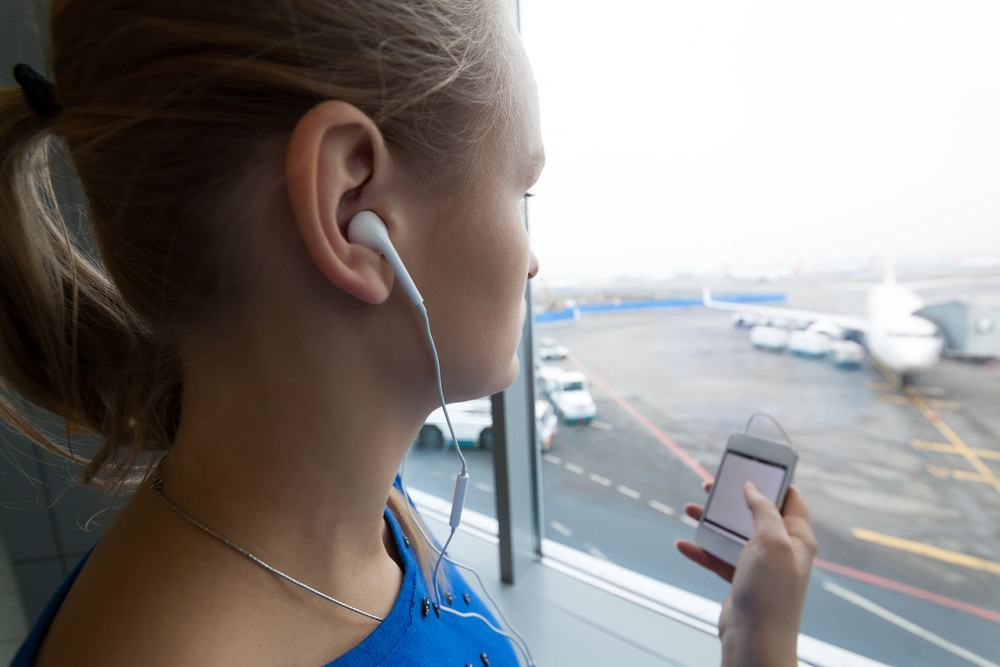 Woman listening to music by the window at airport