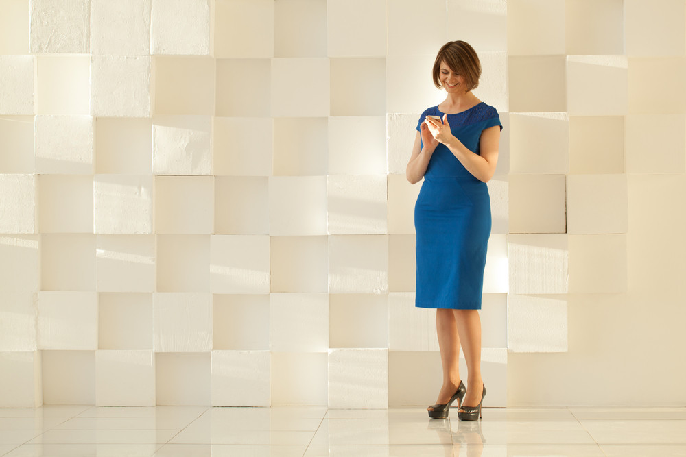 Woman in blue dress standing against modern wall while looking at smartphone