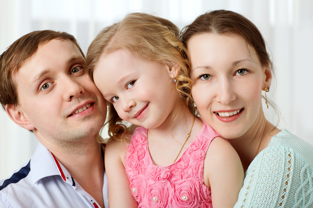 Happy young parents and little daughter