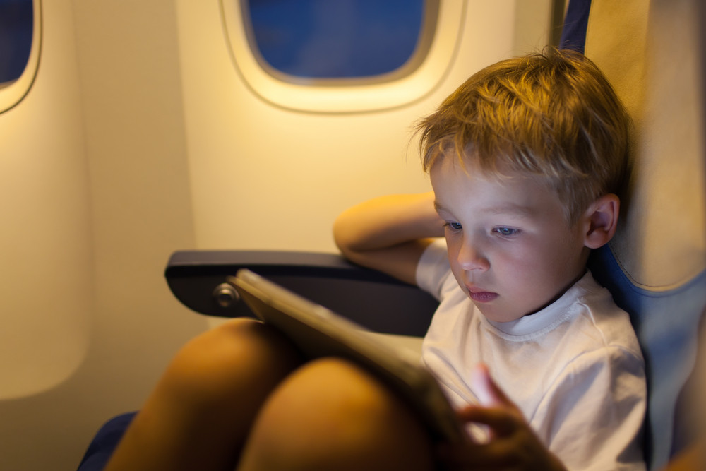 Boy sitting in the plane and using tablet pc