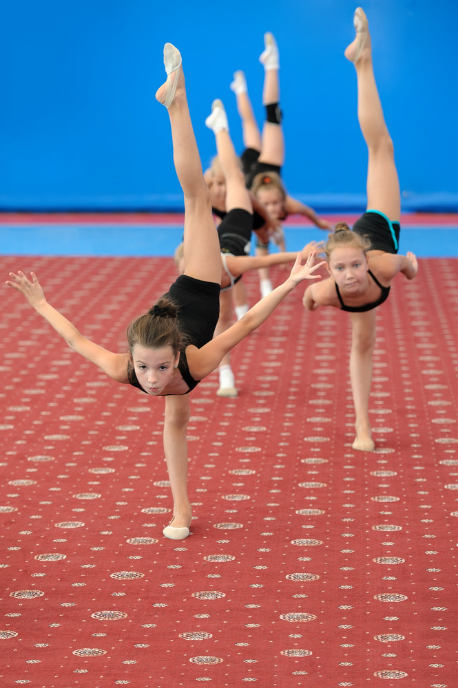 Young female gymnasts doing vertical leg-split