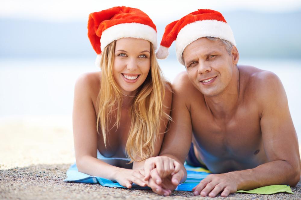 Couple Lying On The Beach In Santa Hats