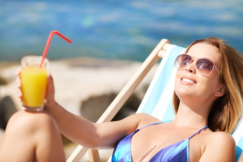 Woman Resting In Deck Chair With A Cocktail