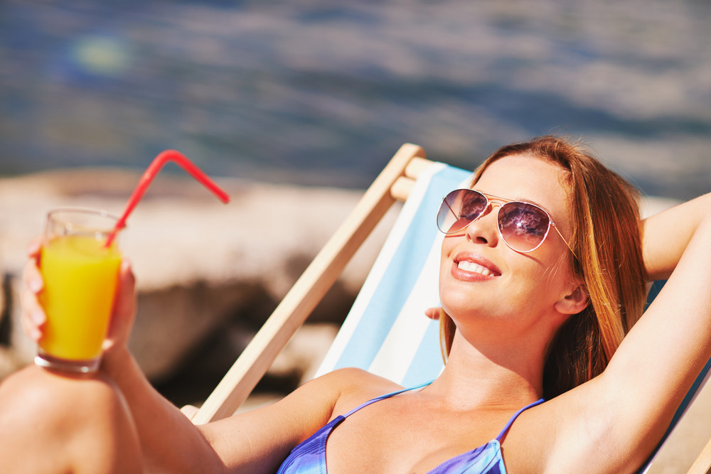 Restful Young Woman With Juice Sunbathing On Beach