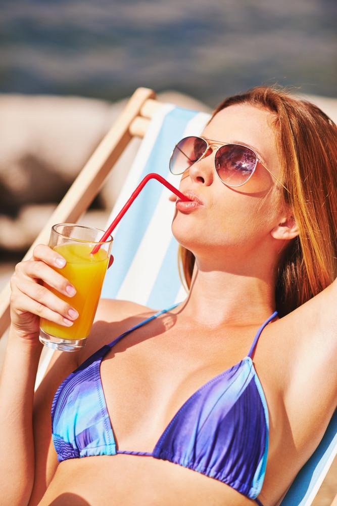 Beautiful Young Woman Drinking Juice While Sunbathing On Beach