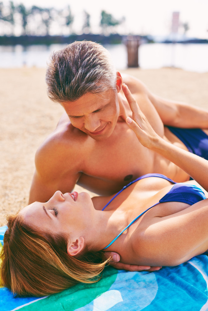 Woman And Man Relaxing On Beach