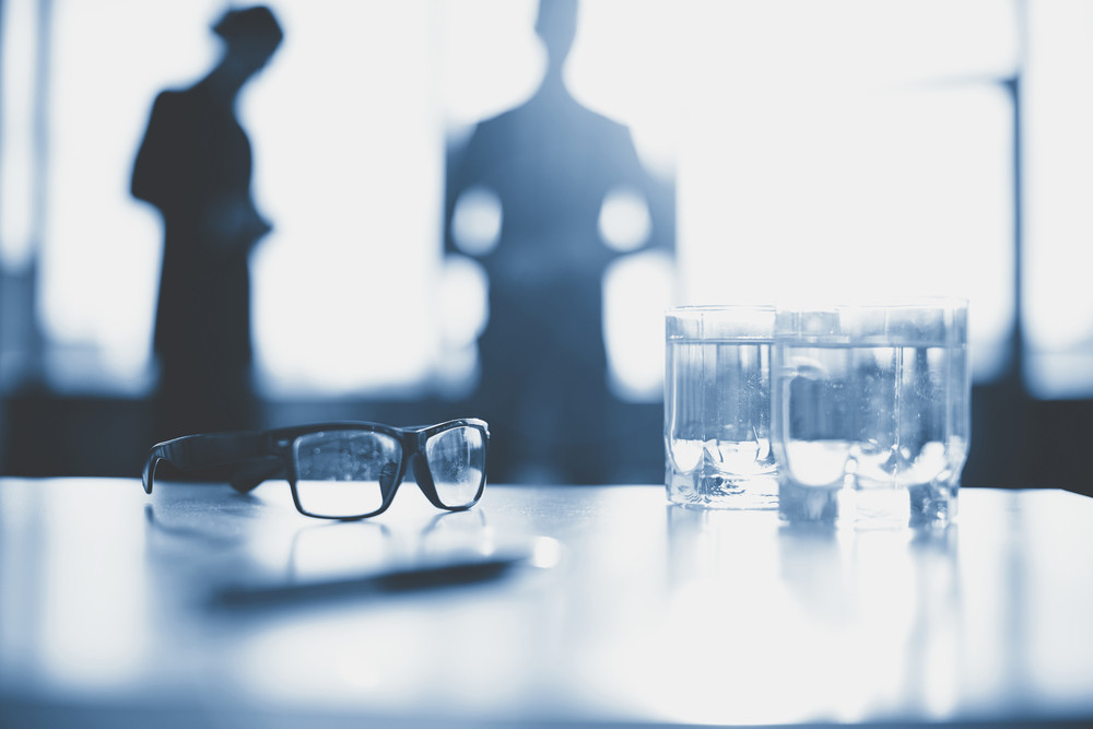 Eyeglasses And Two Glasses Of Water On Desk