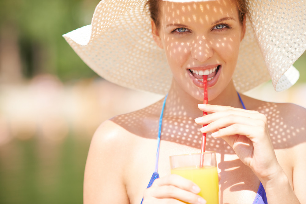 Portrait Of A Woman In Bikini Drinking Juice