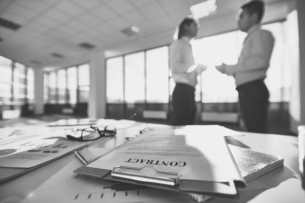 Business Papers On The Desk And Two Men Communicating On Background