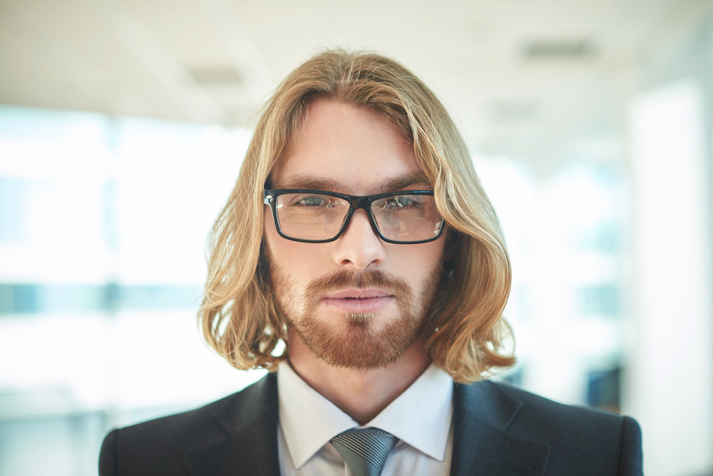 Portrait Of Young Businessman In Eyeglasses Looking At Camera
