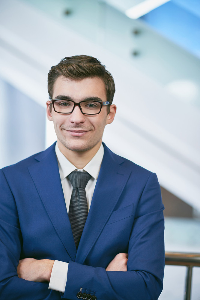 Young Businessman In Eyeglasses And Suit Looking At Camera