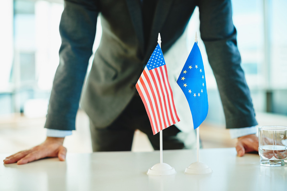 American Flag And Flag Of European Union With Businessman Near By