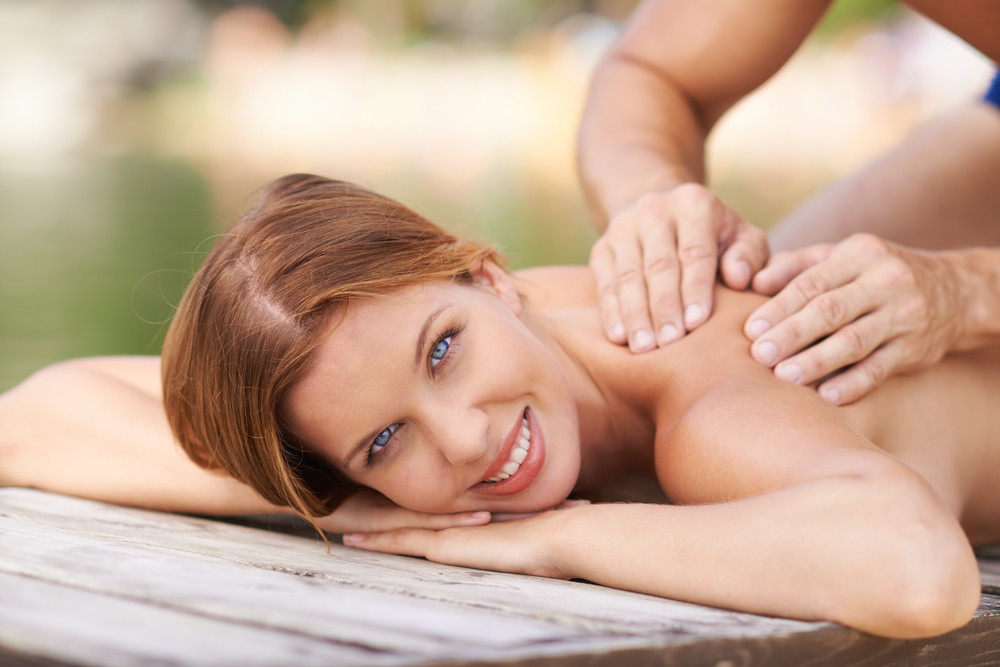 Woman Lying On Pier And Receiving Massage