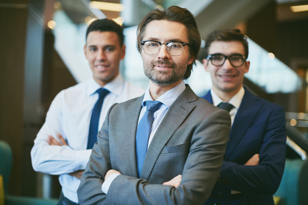 Mature Leader Looking At Camera On Background Of Young Co-workers