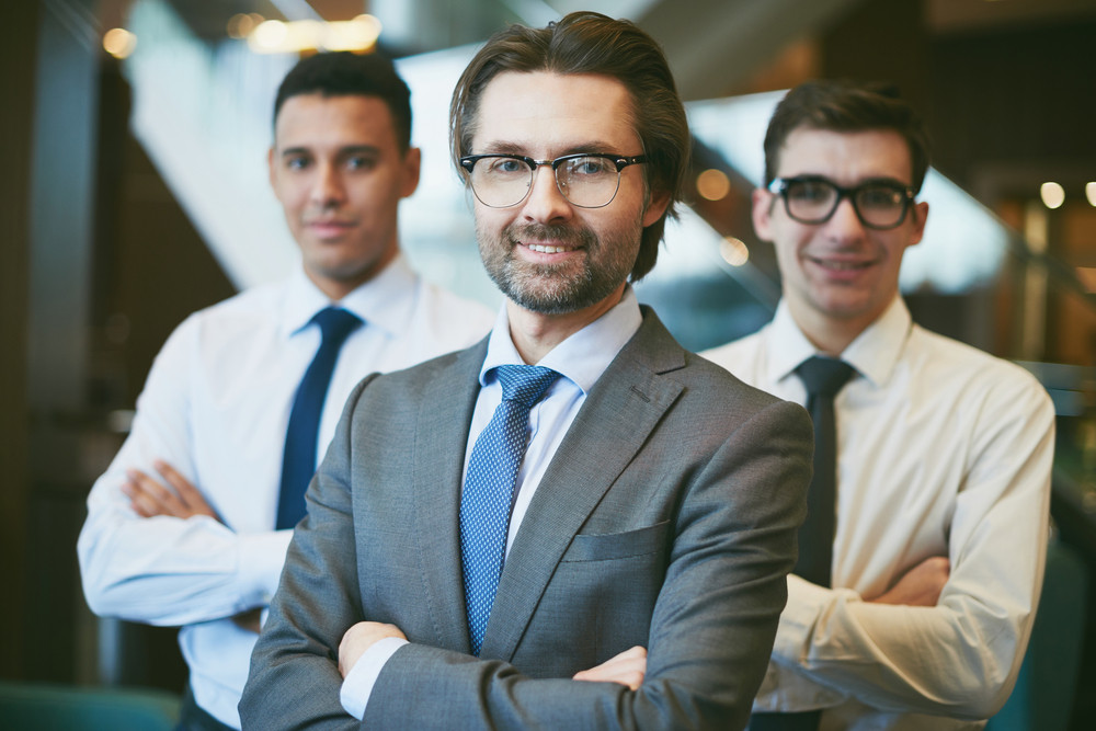 Successful Boss Looking At Camera On Background Of Male Employees
