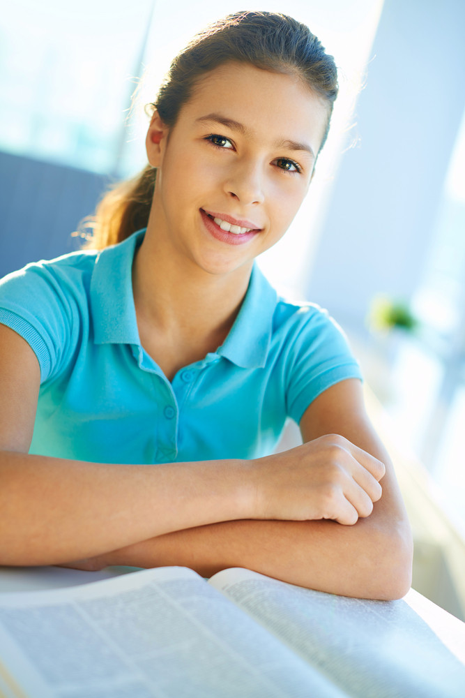Vertical Portrait Of A Smart School Girl With Open Book Near By