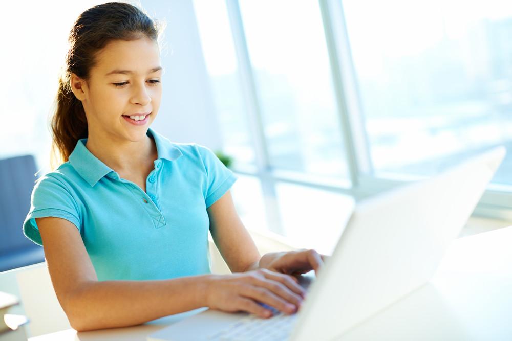 Smart School Girl Typing On Laptop