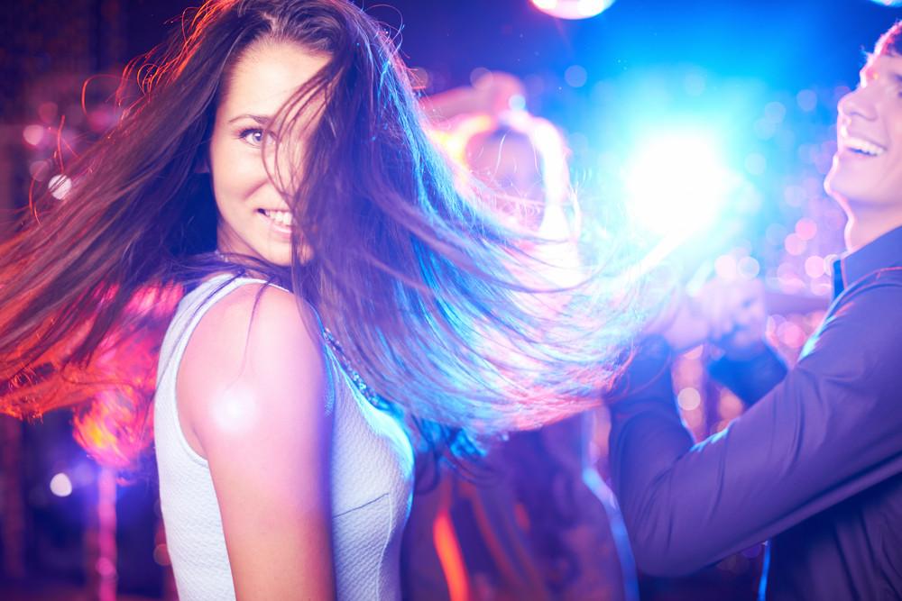 Joyful Brunette Looking At Camera While Dancing In Night Club