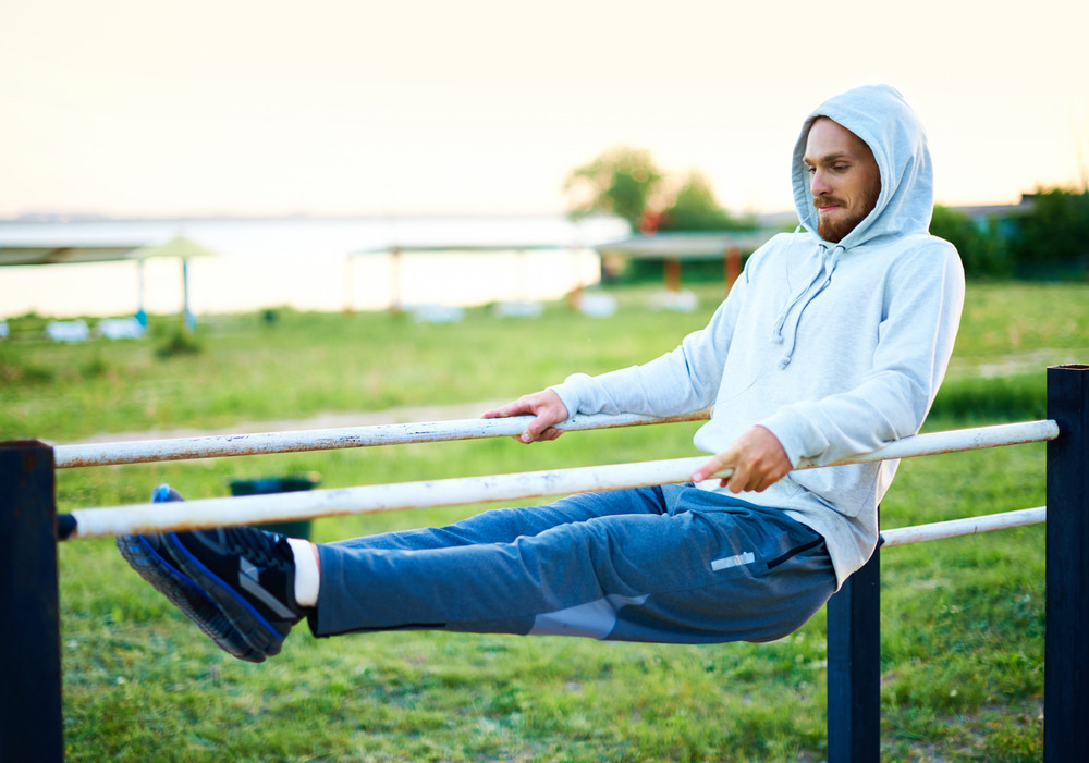 Young Man Exercising On Sport Equipment Outside
