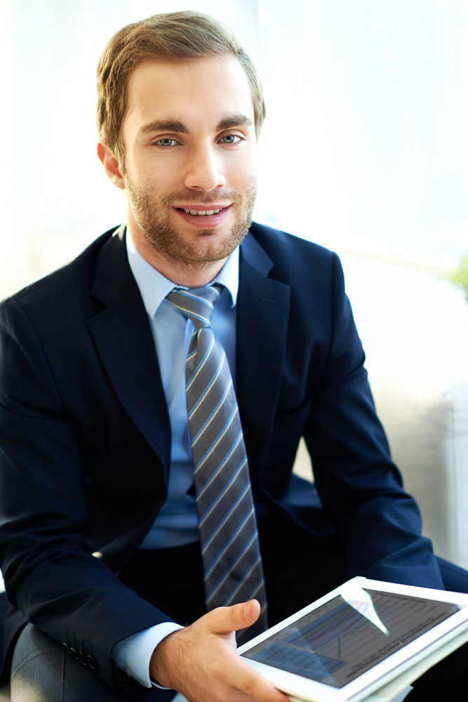 Portrait Of Attractive Businessman With Touchpad Looking At Camera