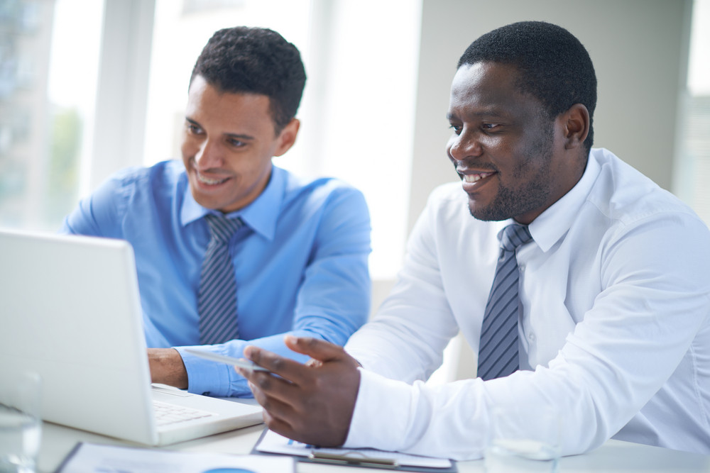 Businessman Of African-american Ethnicity Pointing At Laptop Screen During Presentation