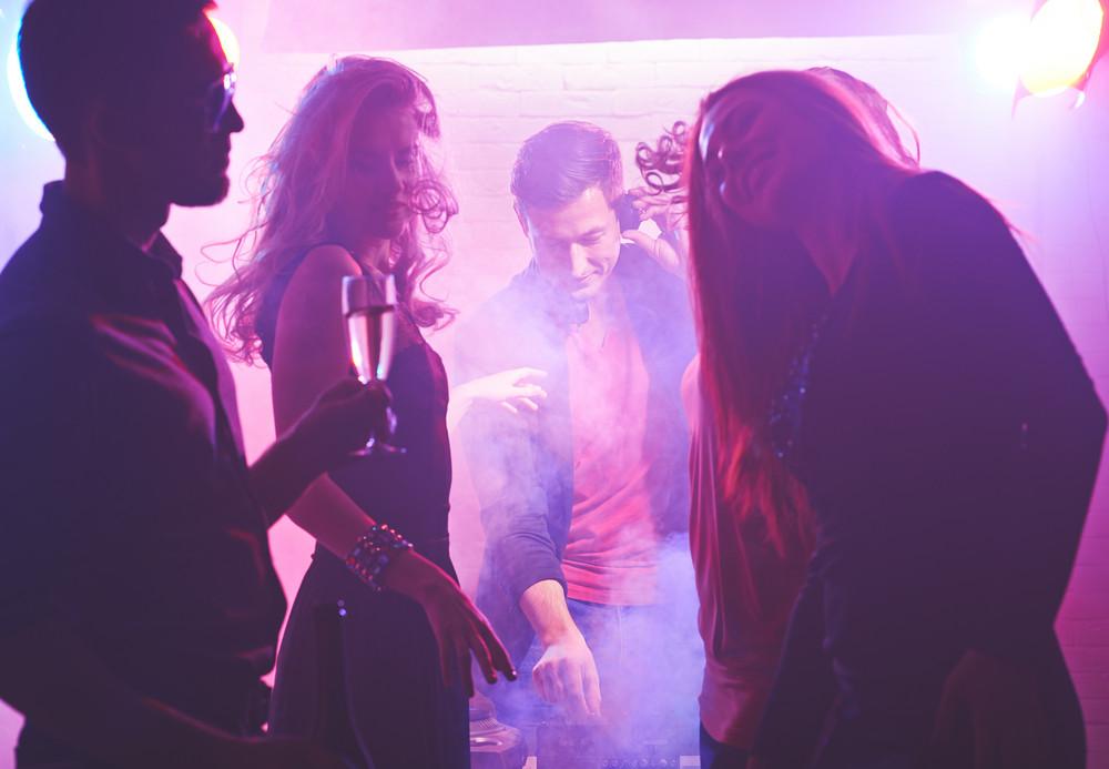 Deejay Working And Cool Girls Dancing In Nightclub