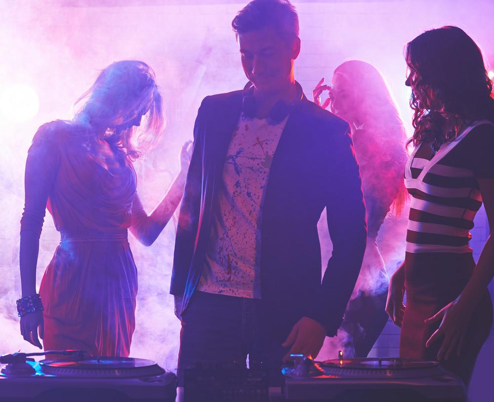 Group Of Girlfriends Dancing In Nightclub With Dj Near By