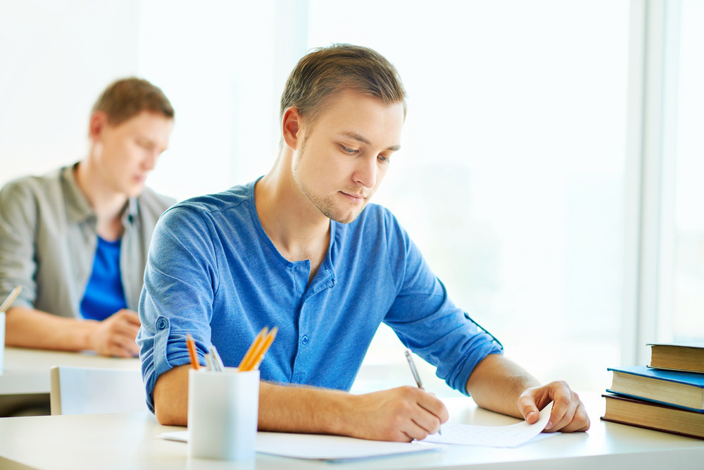 Portrait Of Handsome Student Carrying Out Test At Lesson With Groupmate On Background