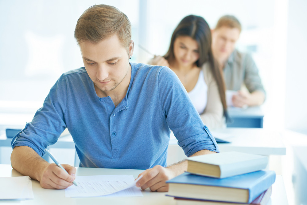Portrait Of Handsome Student Carrying Out Test At Lesson With Groupmates On Background