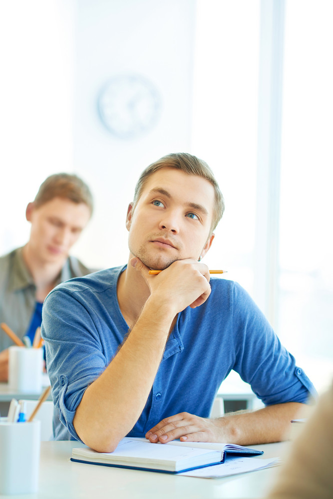 Portrait Of Handsome Student Thinking Of Correct Answer While Carrying Out Test At Lesson
