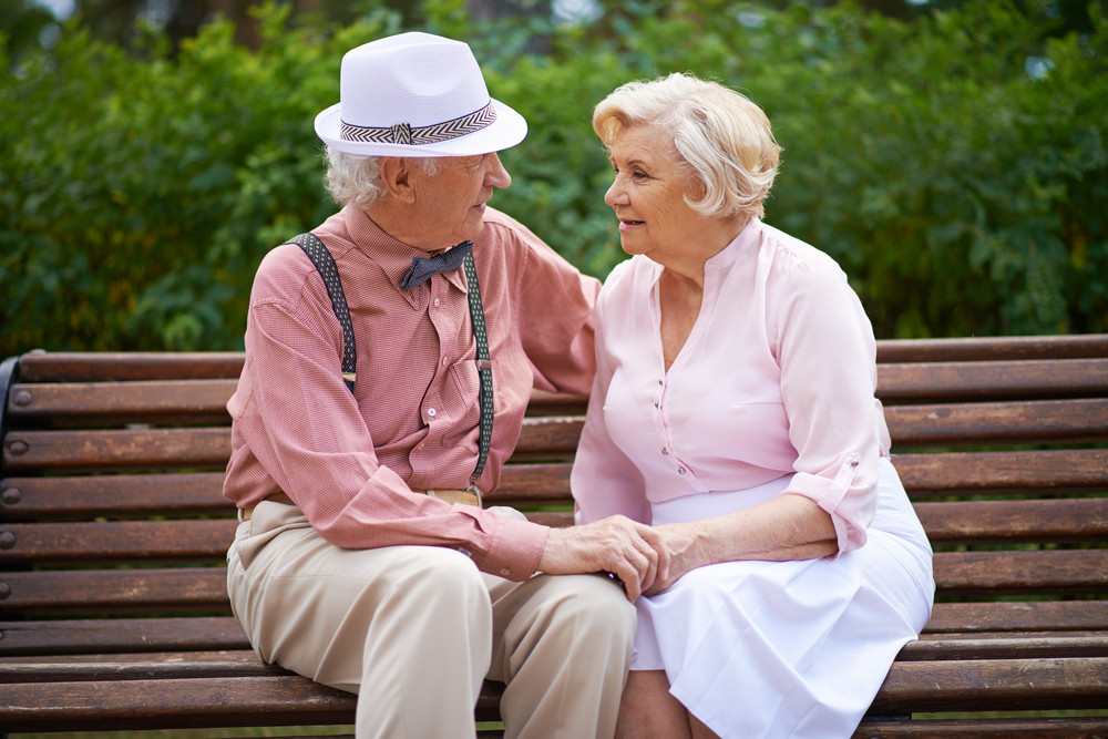 Happy Seniors Talking While Sitting On Bench In The Park