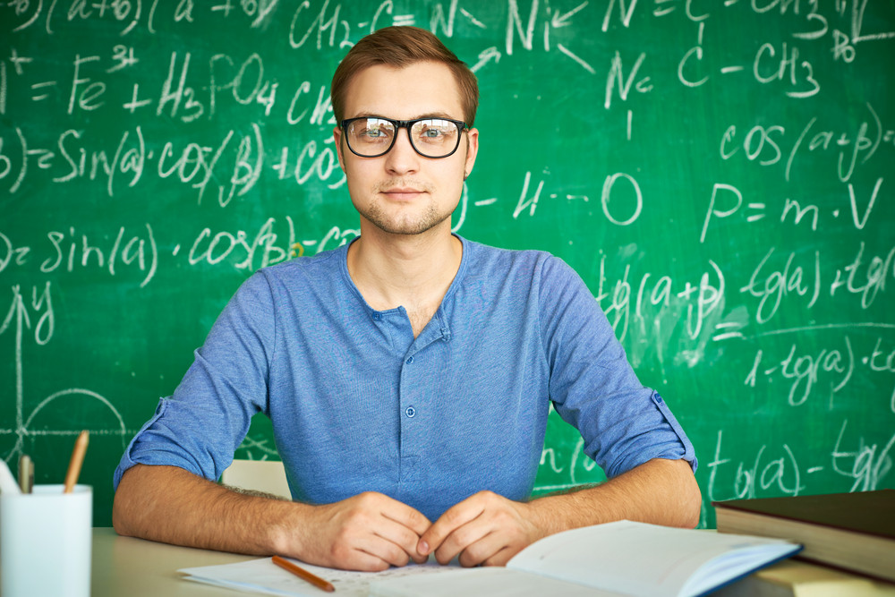 Portrait Of Handsome Student Looking At Camera On Background Of Chalkboard