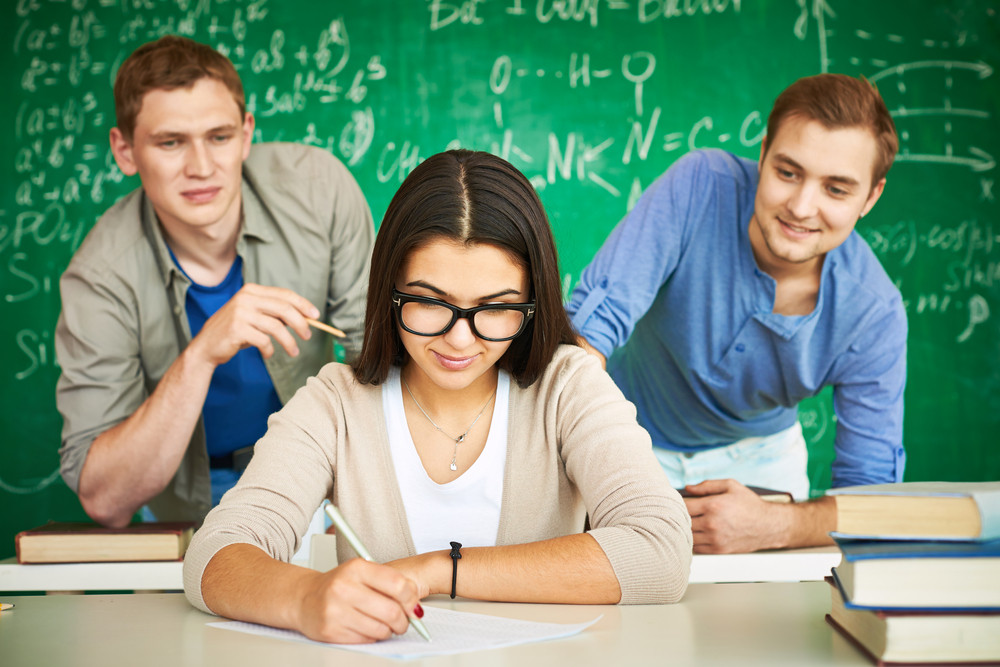 Portrait Of Smart Student Carrying Out Test With Two Guys Behind Looking At Her Paper
