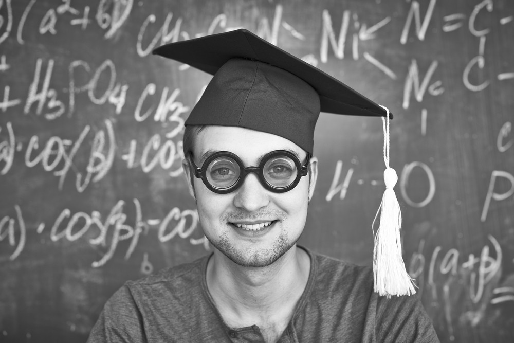 Black-and-white Image Of Handsome Student In Graduation Hat And Eyeglasses Looking At Camera On Background Of Chalkboard