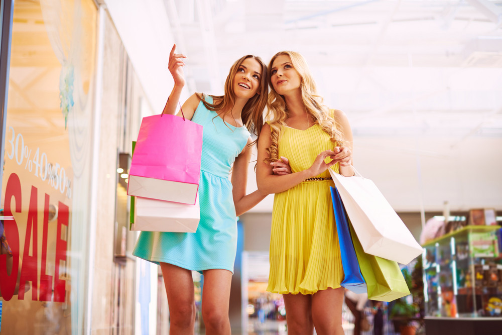 Portrait Of Happy Girls In Smart Casual With Paperbags Spending Time In The Mall