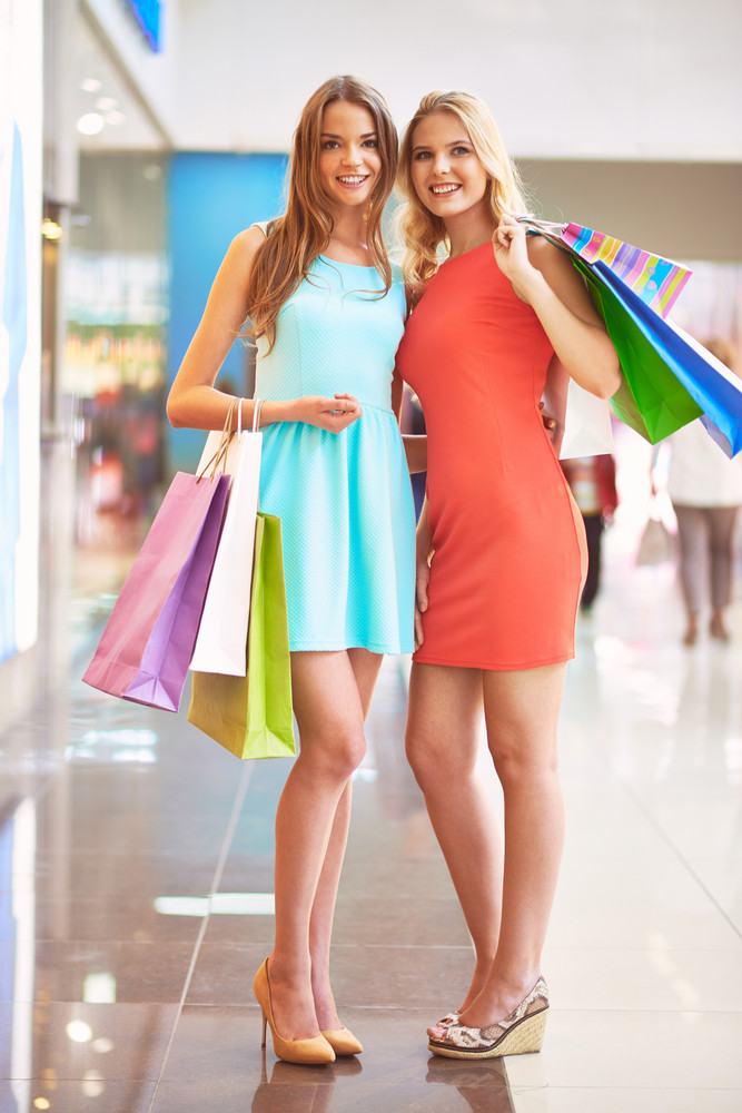 Portrait Of Happy Girls In Smart Dresses With Paperbags Looking At Camera
