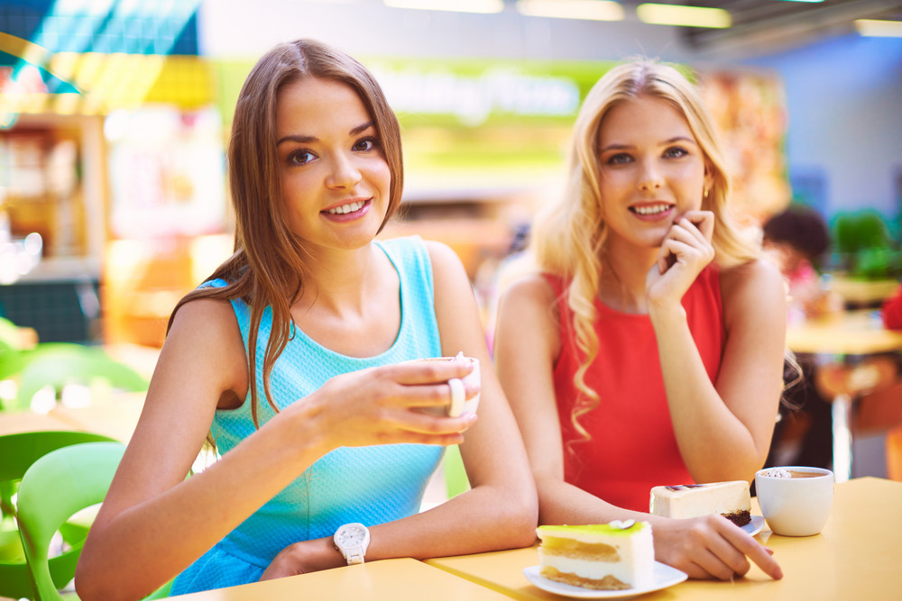 Portrait Of Two Pretty Girls Having Cheesecakes With Coffee