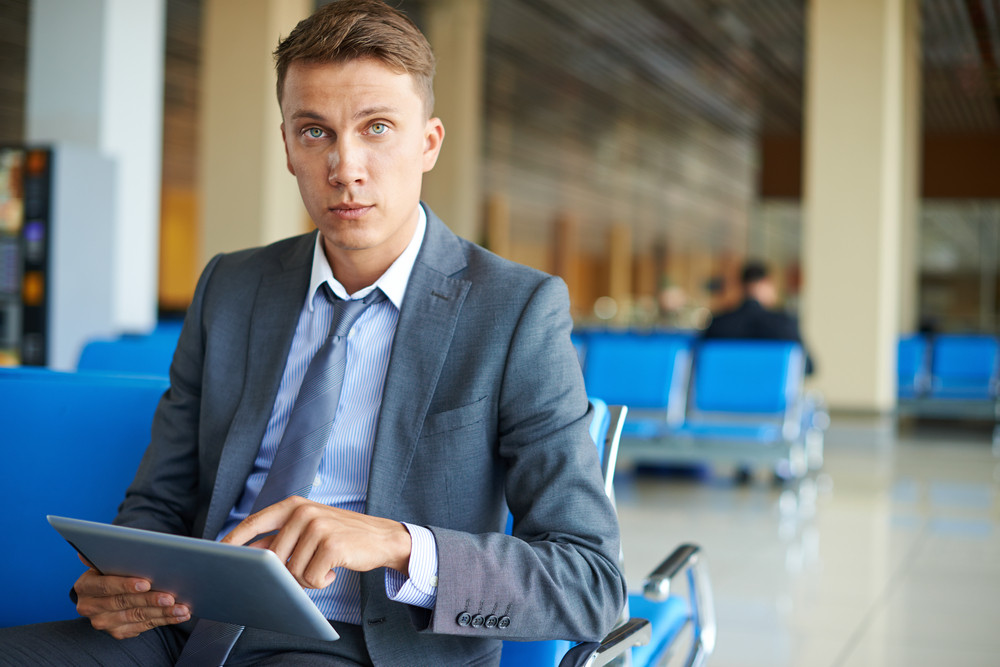 Elegant Businessman With Touchpad Looking At Camera At The Airport