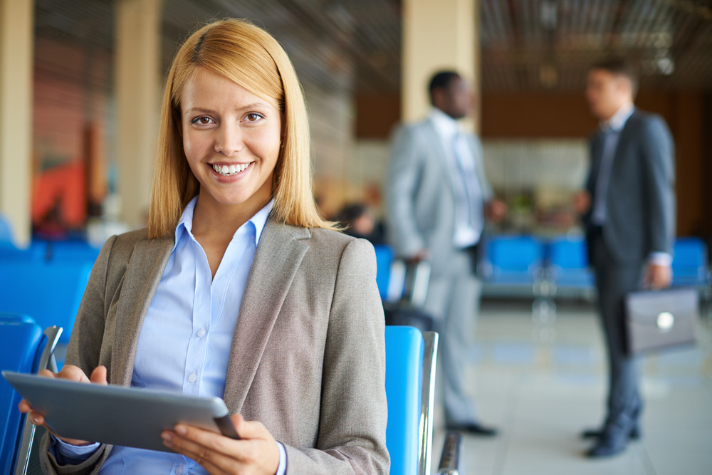 Elegant Businesswoman With Touchpad Looking At Camera On Background Of Two Men Speaking