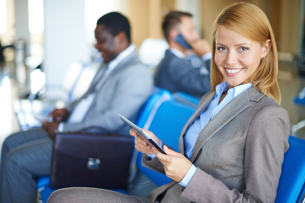 Female Employee With Touchpad Looking At Camera With Two Men Sitting On Background At The Airport