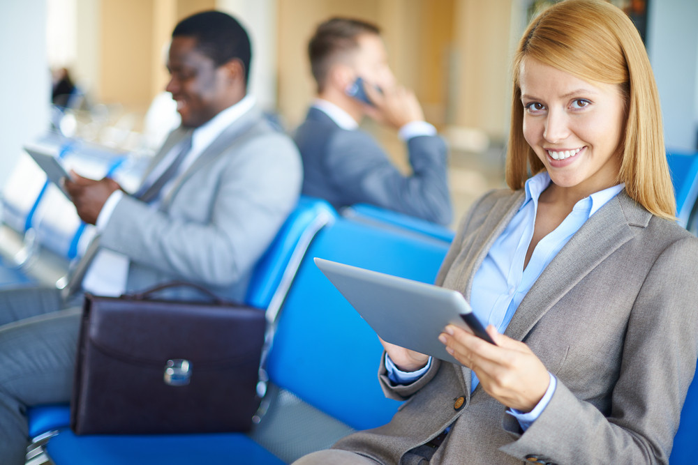 Modern Businesswoman Using Touchpad With Two Men On Background At The Airport